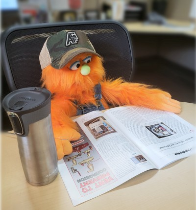 Puppet Testy McSprinkles sitting at a desk to read a magazine
