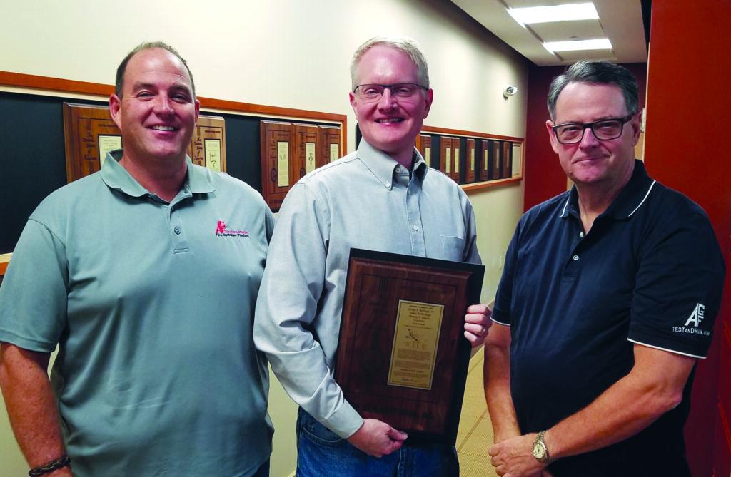 Jim McHugh, Ben Gleeson, and George McHugh pose with the PURGEnVENT patent plaque.